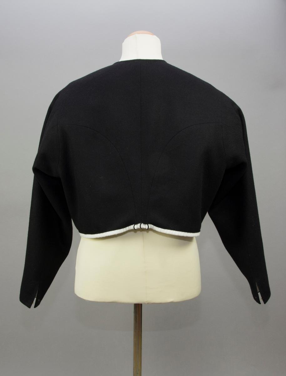 Kvinnotröja till vardagsbruk av svart kläde. Fram- och sidstycket saknar sidsöm och når långt bak på ryggen. Kroksöm mot ryggstycket som har ryggsöm. Ryggstyckets delar smalnar av nedtill i midjehöjd till ett minimalt skört med tre utstående veck. Nederkanten är uppvikt så att det vita fodertyget syns på utsidan. Ärmen är rak. Ärmsprundet knäppt med hake och hyska. Halsringningen är tät och kantad med en remsa av samma kläde. Tröjan knäpps kant i kant med 15 handgjorda hakar och hyskor av mässingstråd, satta varannan hake varannan hyska. Foder av vitt tuskaftat linne. Alla synliga sömmar, stickningar och fastsömnad av foder är sytt för hand. Ej synliga sömmar är sydda på maskin.