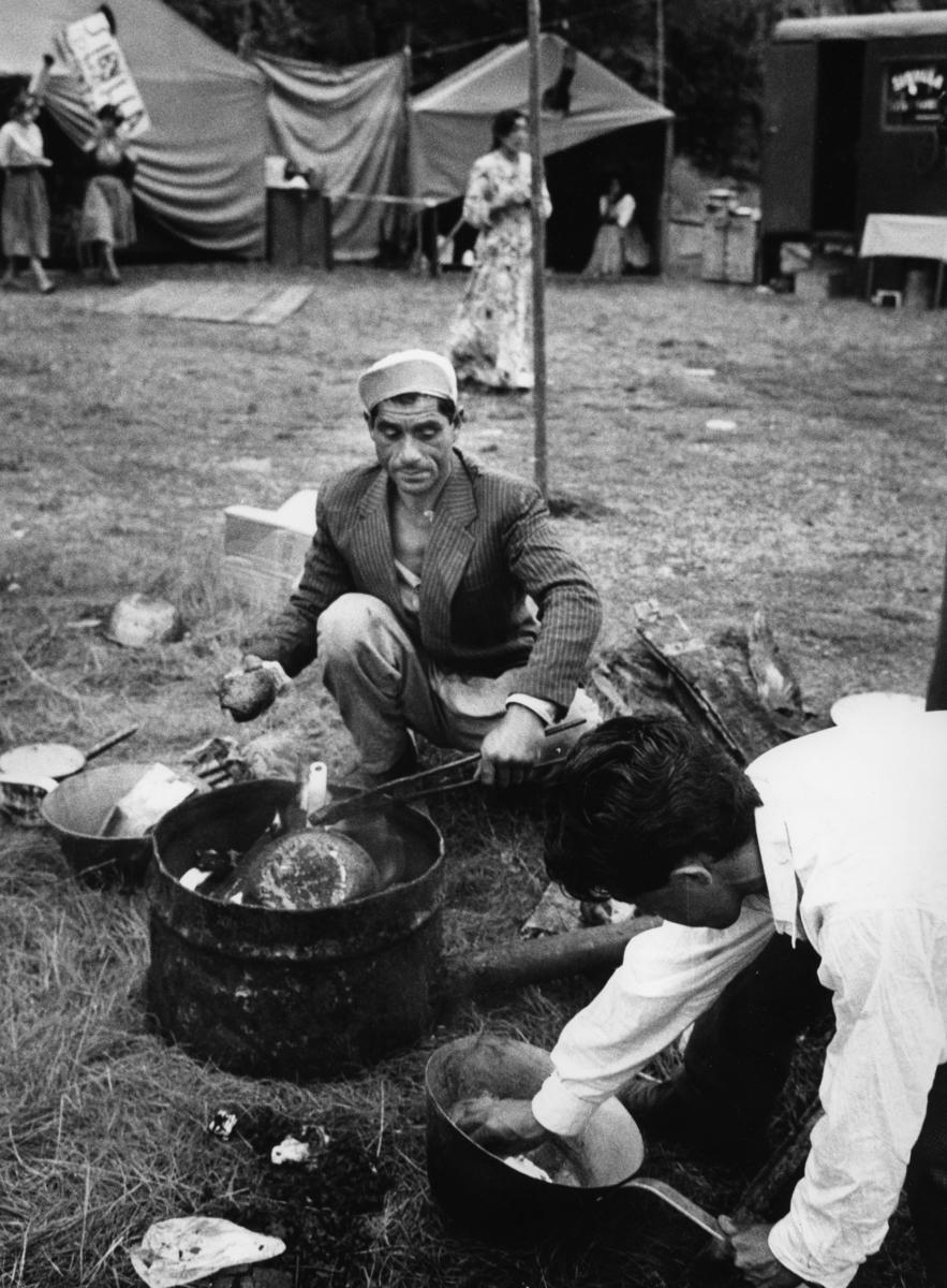 """Romsk man förtenner kärl. I bakgrunden förbereder romska kvinnor spåverksamhet med skylten """"Sibylla"""". Bilden är troligen tagen i samband med inspelningen av TV-programmet """"Du svarte zigenare"""", ett program av Victor Lindgren. Programmet sändes första gången 1960-08-30."""