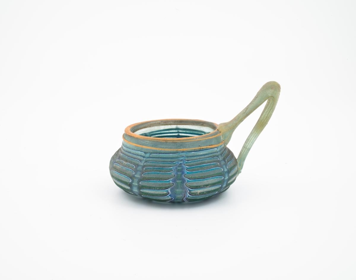 Skål med påsatt hank i turkisfarget, halvgjennomskinnelig glass. Kuleformet, flatklemt korpus med sirkulær munningsrand. Sistnevnte og hanken er dekorert med plastiske, gulfargede striper. På korpus oppstår et rytmisk spill mellom horisontale og vertikale striper i hvit- og blåfarget glass. Overflaten er behandlet med sand for å gi skålen en antikiserende effekt.