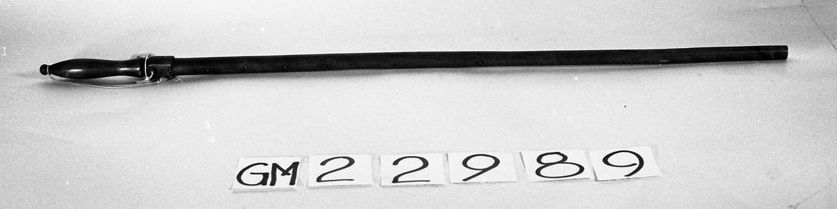 Rund stav i tre med dreid håndtak, messingsåle i enden og små messingnagler med regelmessige mellomrom. På messingsålen er det et stempel som viser skjold med løve og krone, og nær håndtaket er det en utydelig innskrift