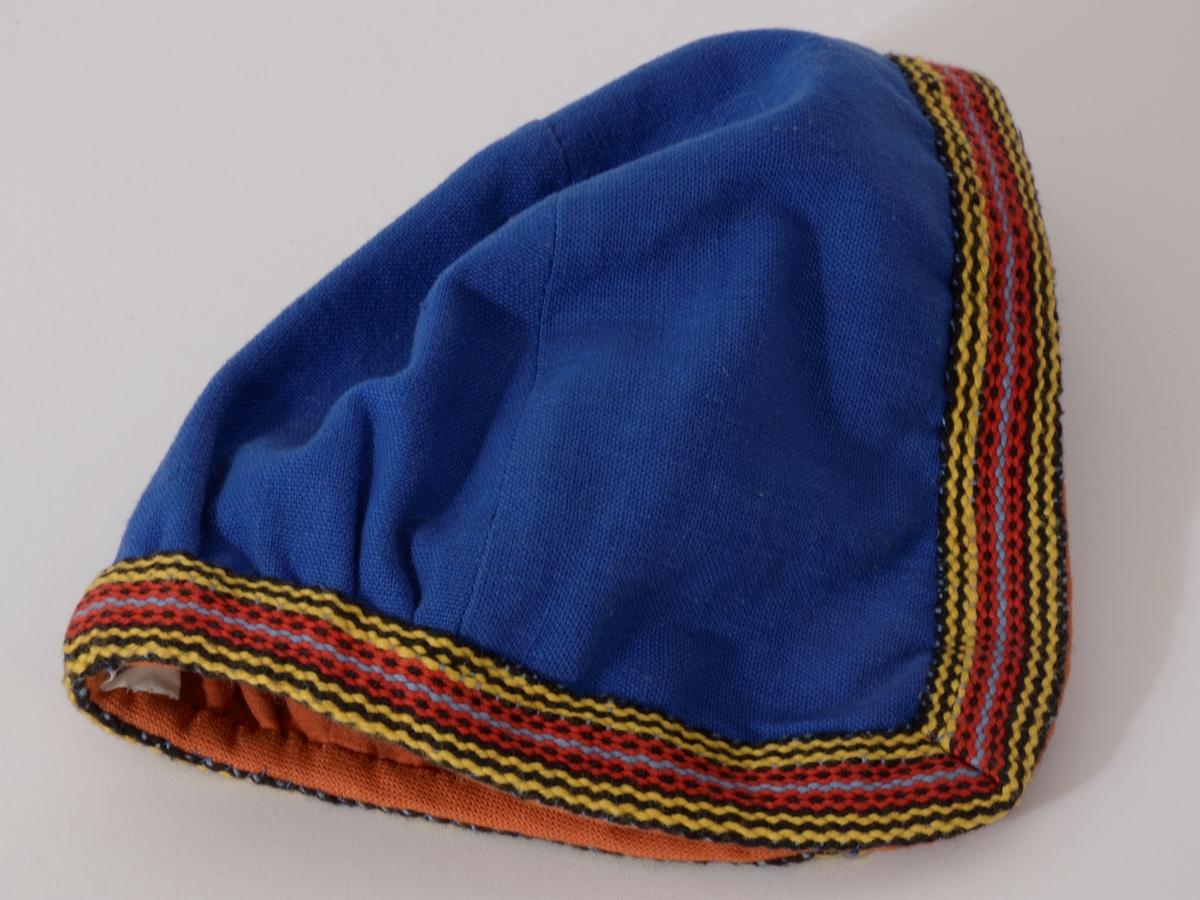 Vestfoldbunad 1932 modell, bomull. Stakk: Maljer med masker og tvunnet snor, flerfargede bånd om ermer, hals og skjørt, belte med  sirkelformet sølvspenne til å hekte, gravert dekor.  Forkle, litt nedsydde legg i livet, flettet rødbrun snor med dusk i endene, mønstervevd bord i gult/brunt nede.  Lue, D-form, bakstykket rynket nede, kantet med bånd, rødbrunt for.