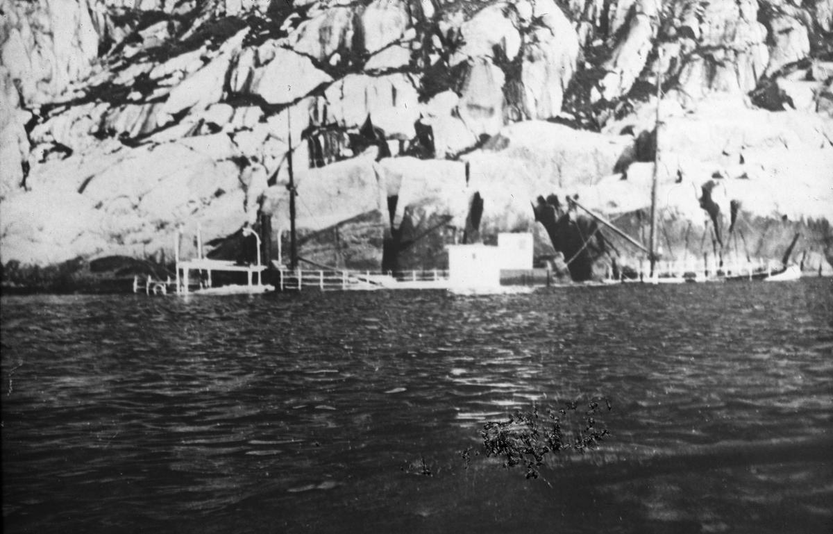 Havarert fartøy i fjordlandskap. Merket EINAR TAMBARSKJELVE.