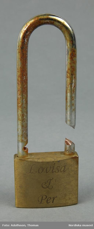 a-b) a) Ett avknipsat fyrkantigt kärlekslås av av mässing, med namn, datum och årtal inristade på båda sidor. På låset sitter b) ett mindre rött hjärtformat kärlekslås av metall, 3 cm brett. /Lena Kättström Höök 2019-01-23