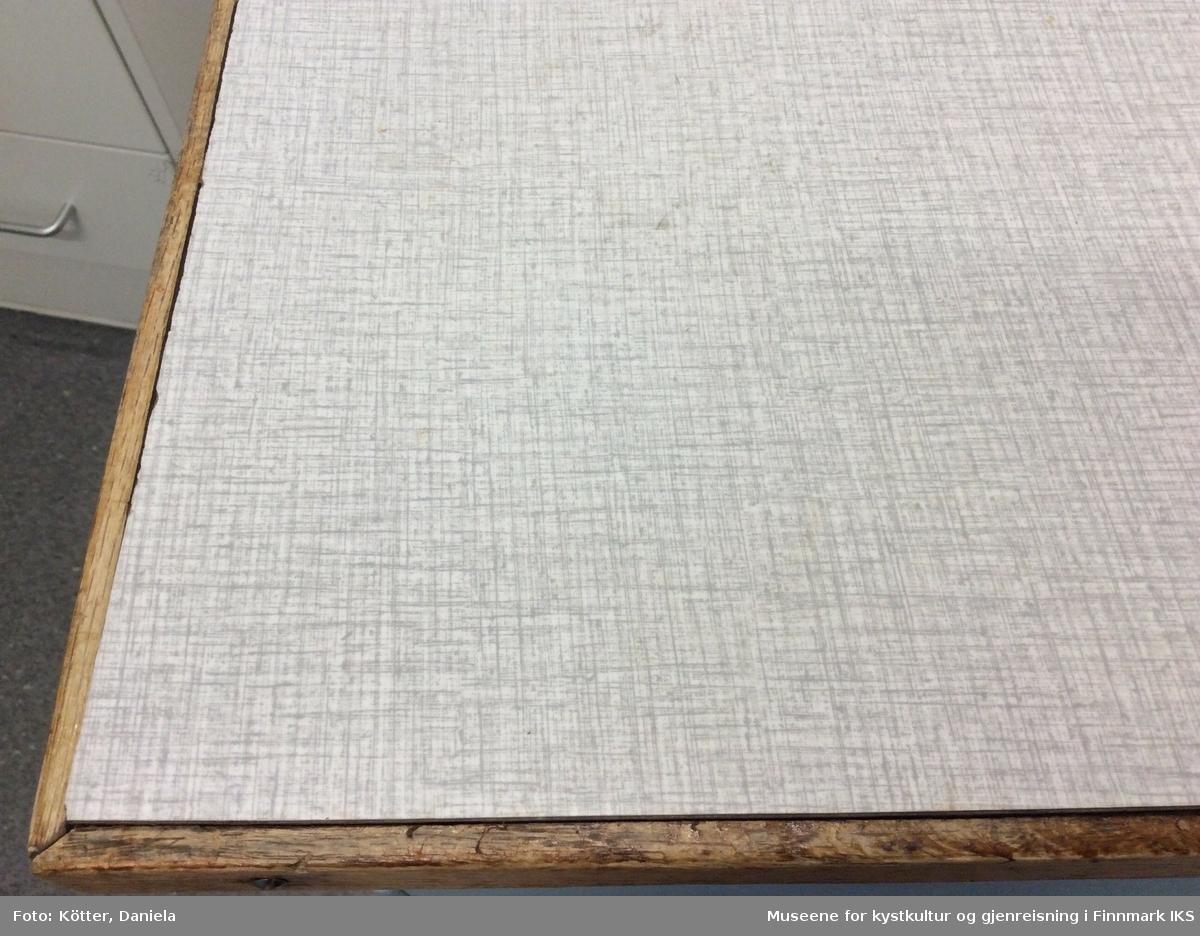 Denne kjøkkenbenken er et av tre sammenhørende kjøkkenmøbler. Det tilhører en kjøkkenbenk med vask og et overskap.  Benken er bygget av tre.  På venstre side er det en skuffe øverst og et skap under med mulighet til to hyller, men bare en som er gjenværende.  Skuffa har en skuffeinndeler av malt tre og er utkledd med blå og hvitt rutet papir.  På høyre sida er det fem skuffer med forskjellig høyde. Den nederste, og samtidig høyeste, skuffe har en utkledning av metall. I midten under benkeplaten befinner det seg et uttrekkbart fjøl. Under det er det ledig rom. Benkeplata er kledd med et grått/hvitt laminatmateriale som ligner på Respatex.  Møbelkroppen er malt hvit mens frontene er malt lyseblått. Håndtakene er enkelt og av lett metall.  Venstre siden av møbelkroppen er bygget av 4 bord som er sammenføyd med not og fjær. På høyre siden er møbelkroppen åpent, noe som tyder på at det var denne siden som var vendt til veggen.