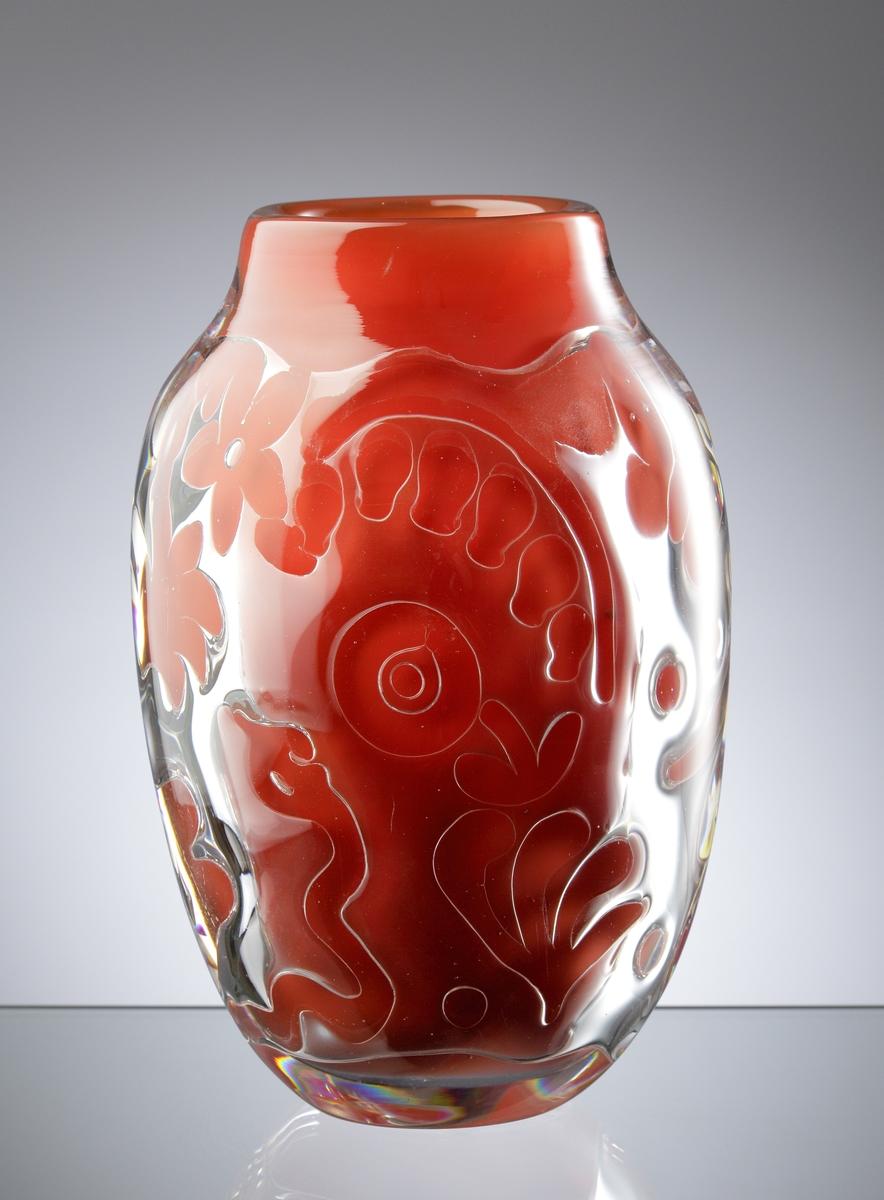 """Röd vas """"Ariel"""" av Edwin Öhrström med nummer 81, med ett luftmönster bestående av stiliserade växter och djur."""