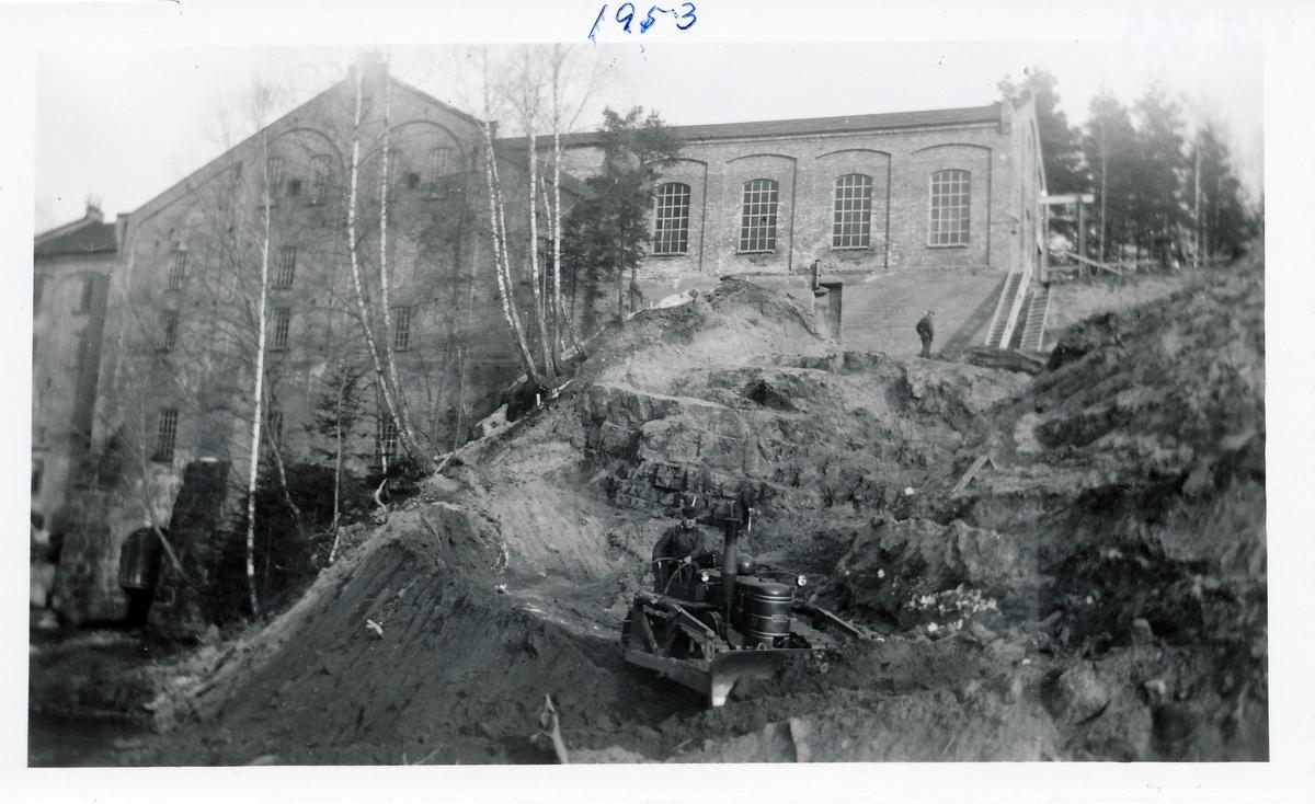 Anleggsarbeid på tomt som graves ut for kraftstasjonen Kistefoss II ved siden av det eldste tresliperiet på Kistefoss. Gammel bulldoser i arbeid i front.