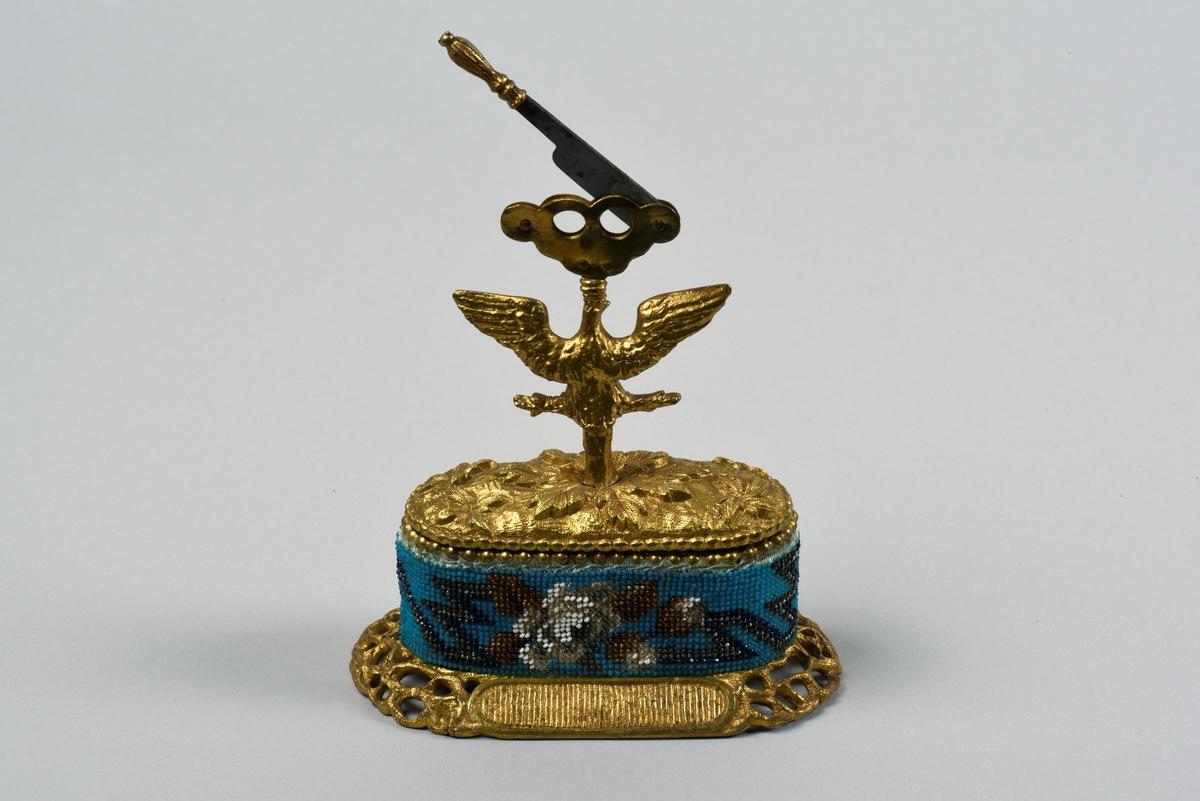 Cigarrsnoppare med ask i två delar. På den ovala asken sitter cigarrsnopparen fästad på en rovfågel. Snopparen är utformad med två hål och skärverktyget är i form av en kniv. Undre delen av asken har ett infällt pärlbroderi med en stiliserad ranka och blommor. Övriga delar är förgyllda.