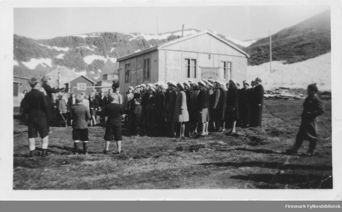 Nordvågen i 1948. 17.mai feiring med Nordvågen Sangforening (stiftet 21.11.1947). Personene har sangerluer på seg.