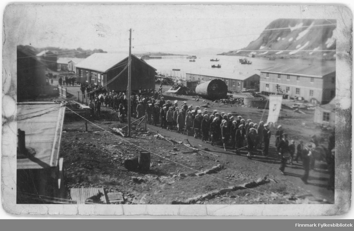 17. mai tog og feiring i Nordvågen i 1948. Vi ser gamle Samvirkelaget, brakka til venstre i bildet. Og Olaf s. Olsens fiskebruk.