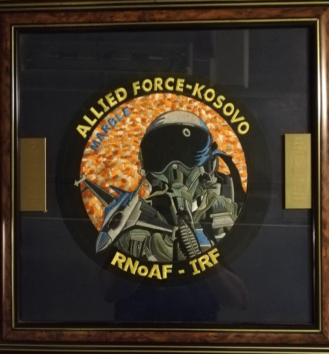 Bildet viser stor patch for Allied Force Kosovo. Messingplater med inngravert callsign for deltakende personell.