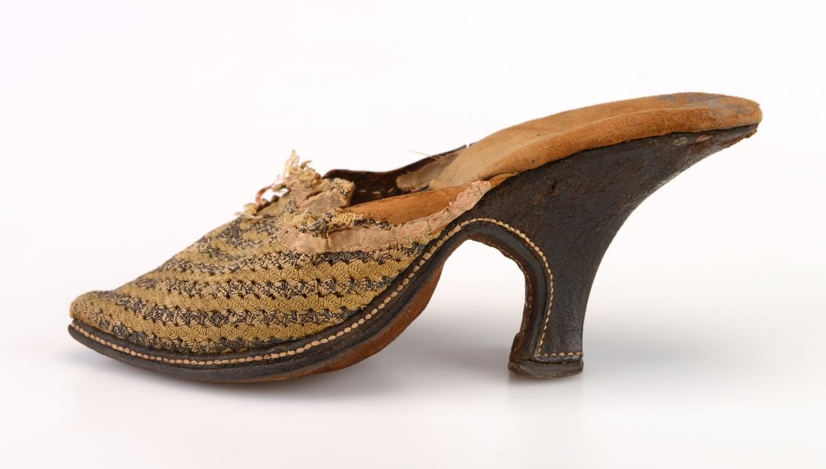En høyhælt damesko av silke og lær/skinn som er åpen bak. Overdelen av skoen er sydd av grønngul silke. Over silken er det silketråd og metalltråd som er vevd sammen (?). Dette utgjør et stripemønster. Stripene går fra sidene og mot midten av skoen. Innvendig er det foret med skinn. Innersålen er av glatt skinn i den fremre delen og semsket skinn på den bakre delen. Yttersålen er av brunt lær. Skoen har snellehæl.