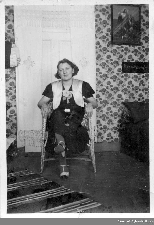 En kvinne sitter på en stol i stua, muligens i Salttjern. Bilde av Jesus henger i veggen. Fine heklegardiner foran døren.