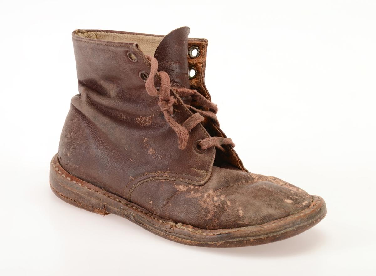 En barnestøvel av brunt lær med høyt skaft. Den er randsydd. Foran er skoen avrundet. I front er det 6 par hull med metallmaljer for snøring. Skoen er snøret med brun, flat skolisse. Under snøringen er det en enkel tunge av skinn. Skoene er foret med ubleket lerretsfor. Innersålen er av lyst brunt skinn. Yttersåle og hæl er av brunt lær. Yttersålen er sydd på. Hælen er stiftet på med metallstifter. Skoen har flat hæl. Det er høyre sko.