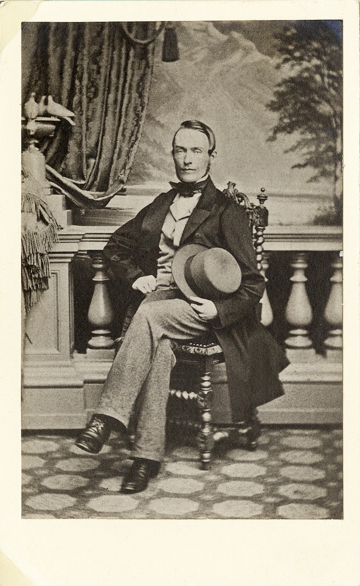 Porträttfoto av en man i mörk redingot med ljus väst och ljusa byxor. Till detta stärkkrage med fluga. Han sitter på en högryggad stol och håller en ljus hatt i ena handen. I bakgrunden syns en balustrad och ett draperi.  Helfigur. Ateljéfoto.