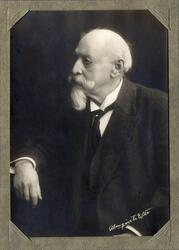 Porträttfoto av en äldre man med pipskägg, klädd i mörk kava