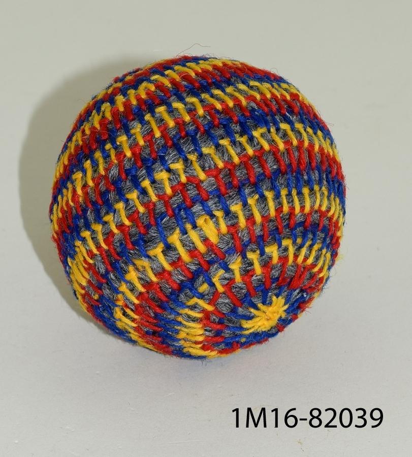Leksak, boll gjord av garn i färgerna röd, blå, gul, grå. Den är handgjord och tillverkad på det sätt som barnen gjorde i Ulricehamn på 1850-talet.
