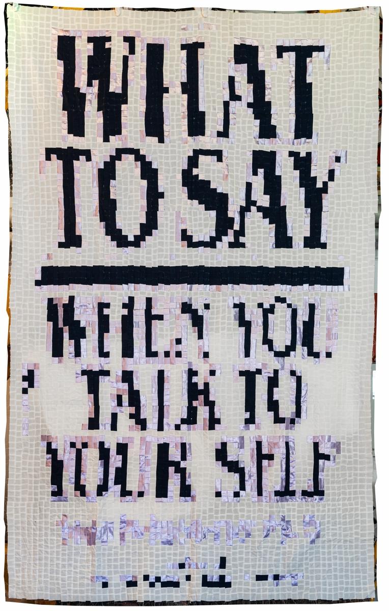 Konstverk i lapptäcksteknik där mönstret formar meningen: WHAT TO SAY WHEN YOU TALK TO YOURSELF. Material: bomull och konstfiber.