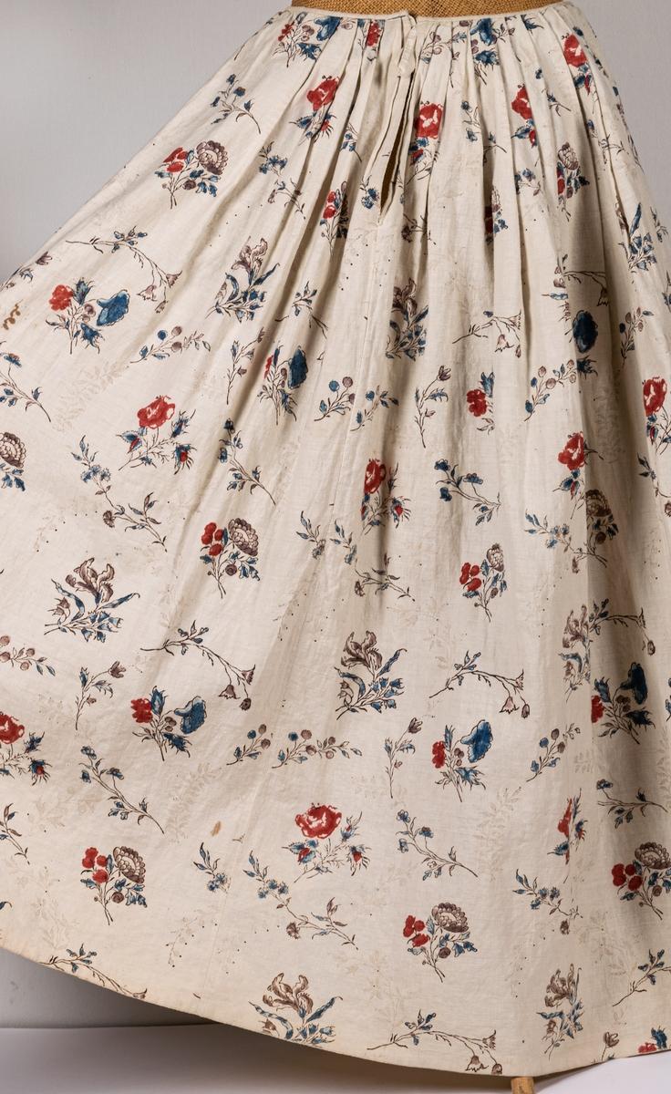Tvådelad klänning, kjol och jacka, i naturfärgat linne med handtyckt blommönster i rött, brunt och blått. Klänningen är från 1700-talet. a) jacka, urringad, knäppning fram, långa ärmar. Fodrad med naturfärgat linne. Lite svängd nedtill. b) kjol, hellång, ofodrad, lagda vecka och smal linning.