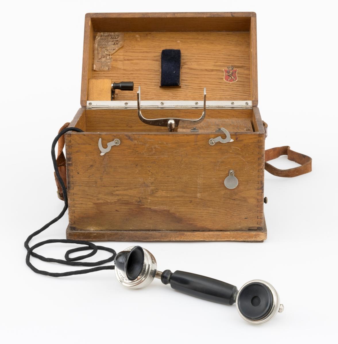 Bærbar felttelefon, antakelig av type som ble brukt tidlig på 1900-tallet. Telefonen er montert i ei trekasse, antakelig lagd av eikematerialer. Kassa har ei botnplate som er 33,1 centimeter lang, 20,2 centimeter bred og 1,5 centimeter tjukk. Ved endene av botnplatas underside er det 19,3 centimeter lange og 3,1 centimeter brede trelister som  gjenstanden sto på. Oppå den nevnte botnplata er det ei 32 centimeter lang, 19 centimeter bred og 16,6 centimeter høy kasse med fingerskjøtte, noe avrundete hjørner. Til denne kassas bakre langside er det hengslet et lokk av samme type materiale og med samme lengde og bredde som kassa. Lokket er 6,1 centimeter høyt. Lokket stenges ved hjelp av dreibare kroker på kassas frontside som vendes, slik at de omslutter skruer på lokkets frontside. Litt lengre neden på kassefronten er det et gjennombrutt hull med 1,3 centimeters diameter, antakelig innføringspunktet for sveiva til telefonen. Dette hukket kan stenges ved hjelp av ei lita, dreibar stålskive når sveiva ikke er i bruk. Da festes sveiva i en trekloss som er innlimt i et hjørne i lokket. Telefonen bæres i ei cirka 2,4 centimeter bred lysebrun lærrein, som er festet i messingknapper, sentralt på den nedre delen av kassas tverrender. At kassa bæres med den riktige sida opp er sikret ved hjelp av smøyestoler av lær høyere oppe på de samme endeflatene. Lengden på bærereima kan justeres ved hjelp av ei nålespenne. Inne i kassa er det antakelig et batteri, skjult under trelokk i to plan. På det nedre er det inntappet en toleddet, forkrommet holder for telefonrøret. Også telefonrøret er forkrommet, med har bakelittkomponenter for håndgrep (midten), øreanlegg og taletrakt. Sentralt på lokkets underside er det pålimt en trekloss med et tjukt svart filtbelegg, som skulle holde telefonrøret på plass under transport. Ellers er det innlimt to etiketter på undersida av lokket. Den ene er et firmamerke som refererer til «AKTIESELSKABET ELEKTISK BUREAU, KRISTIANIA, NORGE». På dette merket e