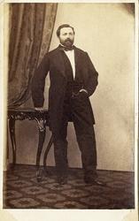 Foto av en skäggig man, klädd i mörk bonjour med väst, stärk
