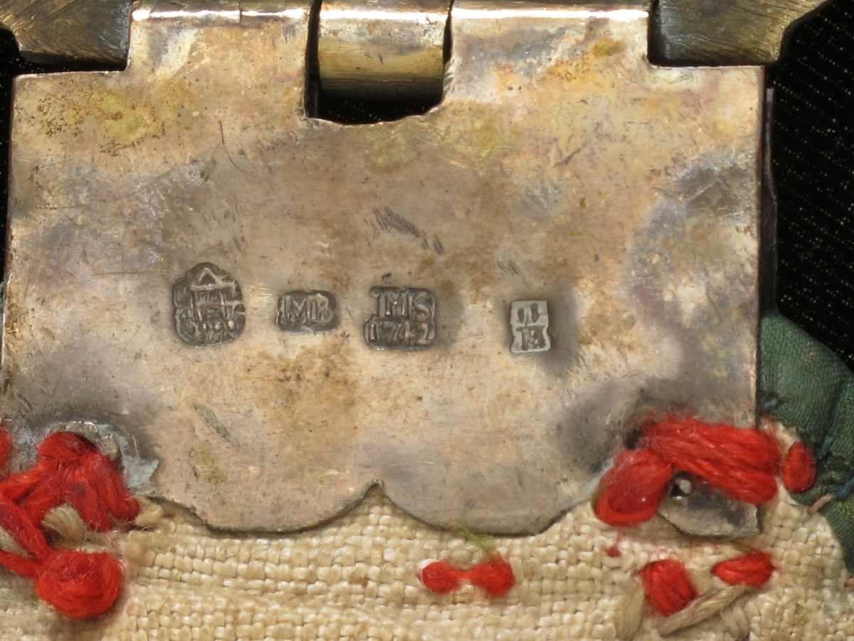 Rødt ulltøy med smalere kanter av grønn silke.  Baksiden foret med grovt lerret, beltet besatt med 17 kvadratiske prydbeslag av forgylt sølv med utstansede rosetter som alle er merket MS 1742.    Beltets ende er avrundet og her er fastsydd en stor sølvspenne, forgylt, rokokko, dens plane del er gravert, bøylen støpt og siselert, har motiv masker og atlanter.  Stempler.  Ved beltets andre ende en fillet tøylapp til å feste spennen på, fra denne henger det ned langt rødt ullbånd av samme bredde som beltet, kantet med grønn silke, påsydd fire forgylte sølv (?) knapper med utstanset kors.  Nederst er båndet avrundet, her er festet et sølvbeslag, gravert med akanthus og arkitektur, forgylt med tre gjennombrutte løv hengende på enden. Stemplet IMS 1742.  De tre gjennombrutte løv nederst på beslaget på anhenget:  Kronet M, tilsvarer de 12 maler med kronet M (Maria) som eies 1978 av fru Sigrid Aamli, Skarpnes.  De står i kontrast til selve endebeslaget, som har gravert akantus og arkitektur.  Er de satt på av brukeren eller overført fra eldre belte eller smykke? (RH nov. 1978)