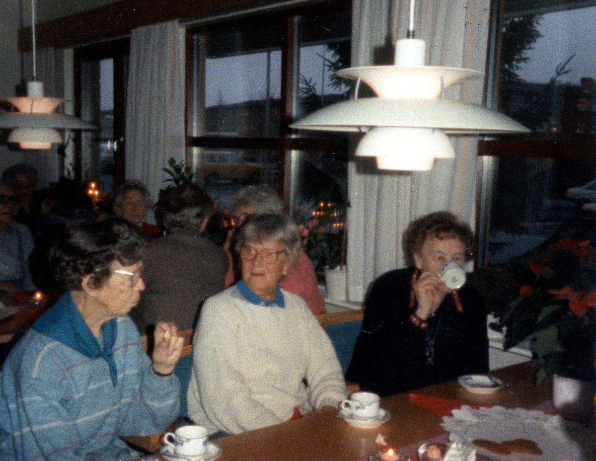 Fikastund i Brattåsgårdens matsal (Streteredsvägen 5), 1980-tal. Från vänster sitter Alma Persson (1910 - 1987), Edit Bernhardsson (1911 - 2000) och Maria Brattberg (1904 - 2000). I taket hänger en vit PH-lampa, formgiven 1924 av den danske arkitekten Poul Henningsen.
