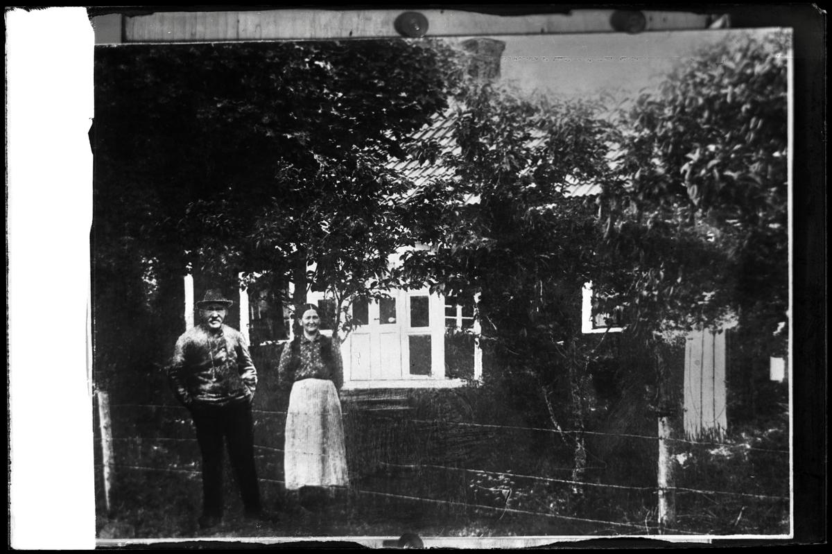 Äldre par framför hus