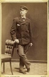 Foto av en ung man i kavajkostym med fluga och skolmössa. Vi