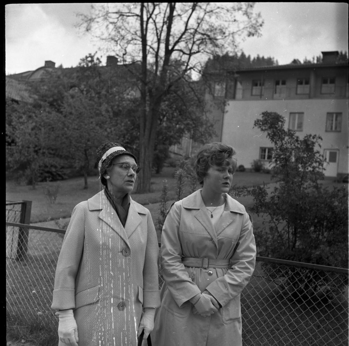 En äldre kvinna och en kvinnlig konfirmand står på Sjögatan i Gränna.