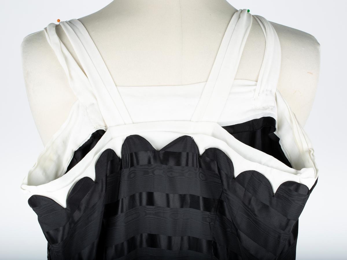 Selskapskjole. Lang gallakjole, i sort silke og silkegeorgett. Smale hvite skulderstropper og hvit kant øverst på livet. Trangt liv, avsluttes med tungekant mot hvitt georgettestoff.  Skjørt i 6 volangklippede breddersom avsluttes med buer/tunger mot et et innfelt stykke i livet. Innfelte stykker nederst på skjørtet på grunn av vidde.   Stoffet strukturvevet - striper - satin og moiré vev.Sydameprodukt eller hjemmesydd, maskinsøm, kasting og opplegg for hånd.  Små revner ved skuldersøm, brystsnitt  og skjøt-sømmer nede på skjørtet. Ellers i bra stand. Eiere og givere:  Astri Breder Berg f.ca.1942 og Jens Christian Berg. Oppegård. Tidligere eier og bruker:Enten  Ingeborg Berg f.18.10.1897, mor til Jens Christian Berg, elller Margit Breder f.12.2.1907.  Kjolen ant. brukt i Rebekkalosjen.