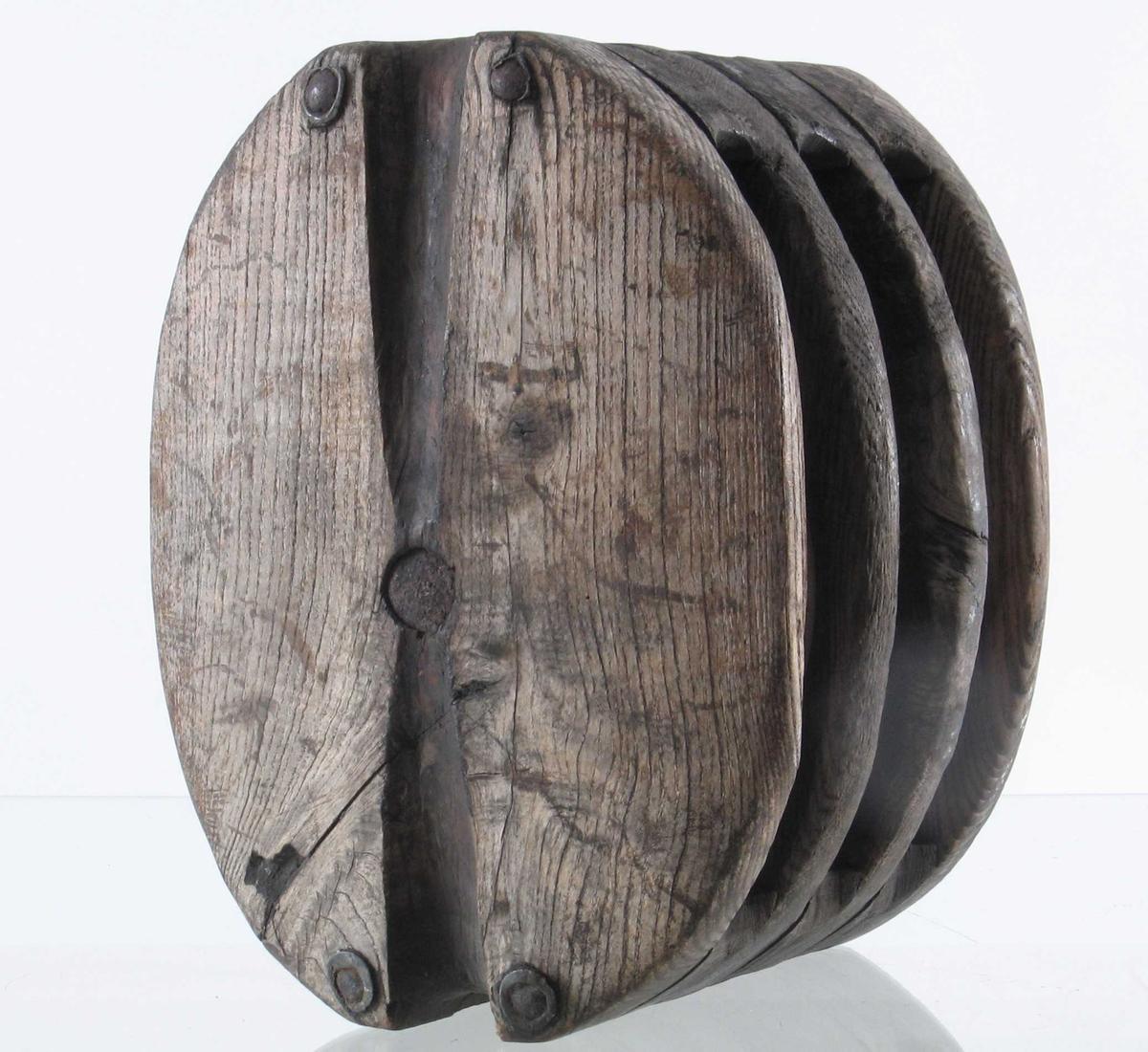 Blokk, 3 skåren.  Ask  med 3 skiver av  pukkenholt.   Tilstand: slitt, grå i treet, alle skivene har  sprekker.   Jern  bolten rusten.  høsten 1932.