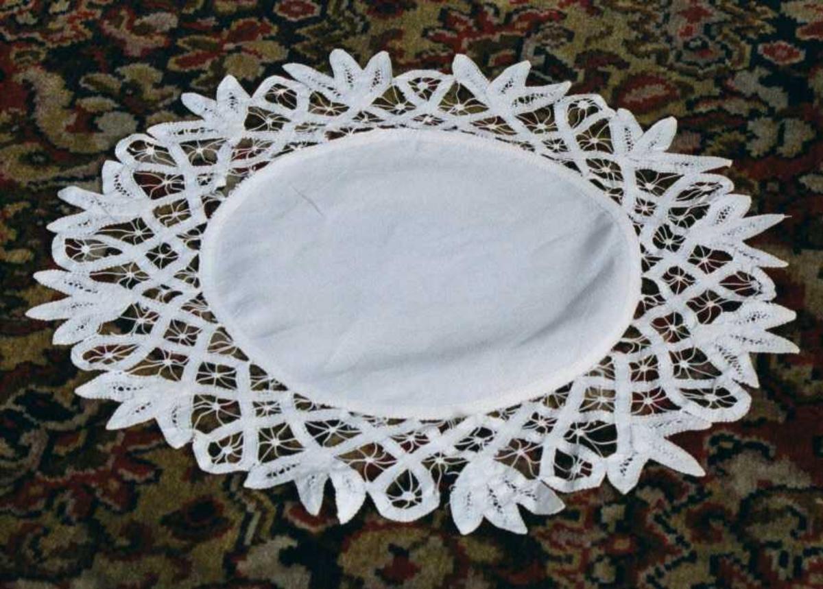 Brikke av lin, med  kniplingskant.  Sirkulær  duk med en bred bord av åpne ruter og langs kanten trebladet  form.  Tilstand: stivet og ren, god.