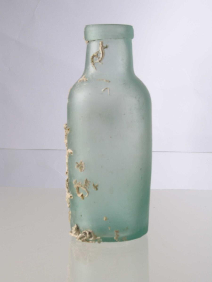 Medisinflaske,   Glass,  lyst grønt.    Sylindrisk  flaske i forholdsvis tykt glass, runde skuldre, bred hals med munningsbrem. Begrodd under  bunnen og i den ene halvdel av korpus. Var halvfull  av et hvitt steirkiant pulver, resten råttent sjøvann  og   kork.    Tilstand: innholdet tømt p.g.a. lukten, flasken gjort ren.