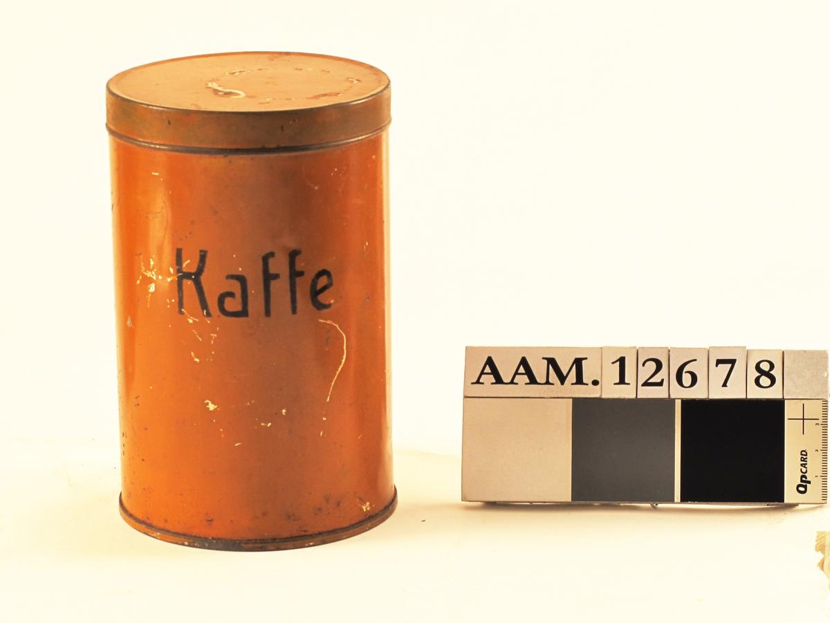 Kaffeboks med kornkaffe,  krigen 1940 45.    Blikkboks, malt oker, sort tekst:   Kaffe.   Sylindrisk boks med flatt lokk, innhold: vel  halvfull med brent kornkaffe, antag. fra krigens  siste tid.