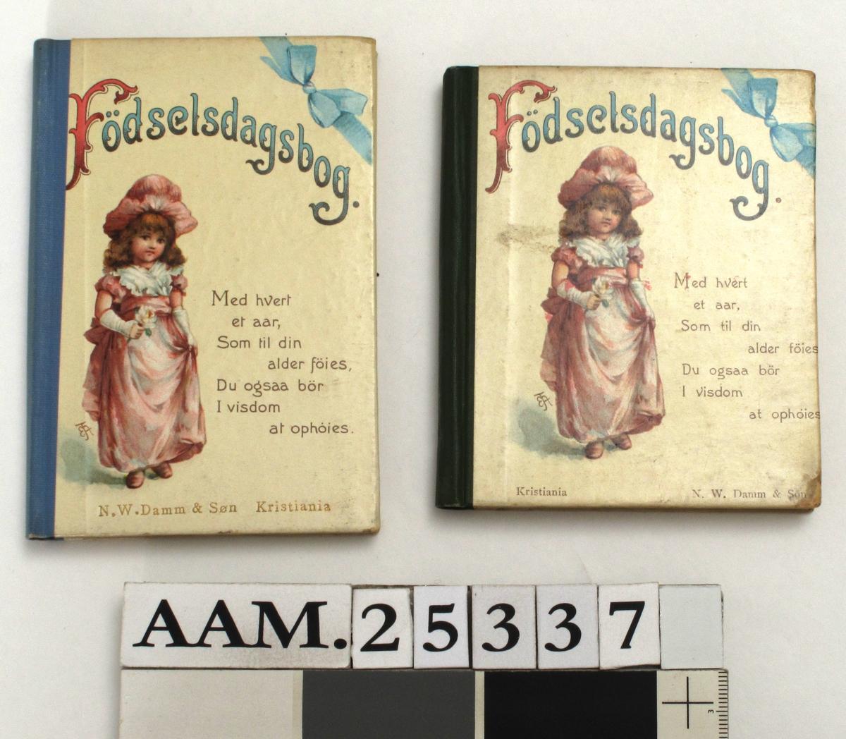 """Fødselsdagbog, 2 stk. N. W.Damm & Søn, Kria. ca. 1904.  a)  dedikasjon """"  Til moder fra Gunnar. Julaften 04 12 011. 11  Rygg grønn shirting. 10,7 x 9 cm.  b)rygg blå shirting. 12,2 x 8,5 cm.  Bøkene er en tanke forskjellige og representerer to forskjellige utgaver.  a) litt slitt, b) god Tilstand.    a) Tilhørt fru Sophie Krøger, f. Olsen  b) frk. Ingrid Krøger eller søsteren Margr. Frederikke Strøm, f. Krøger."""