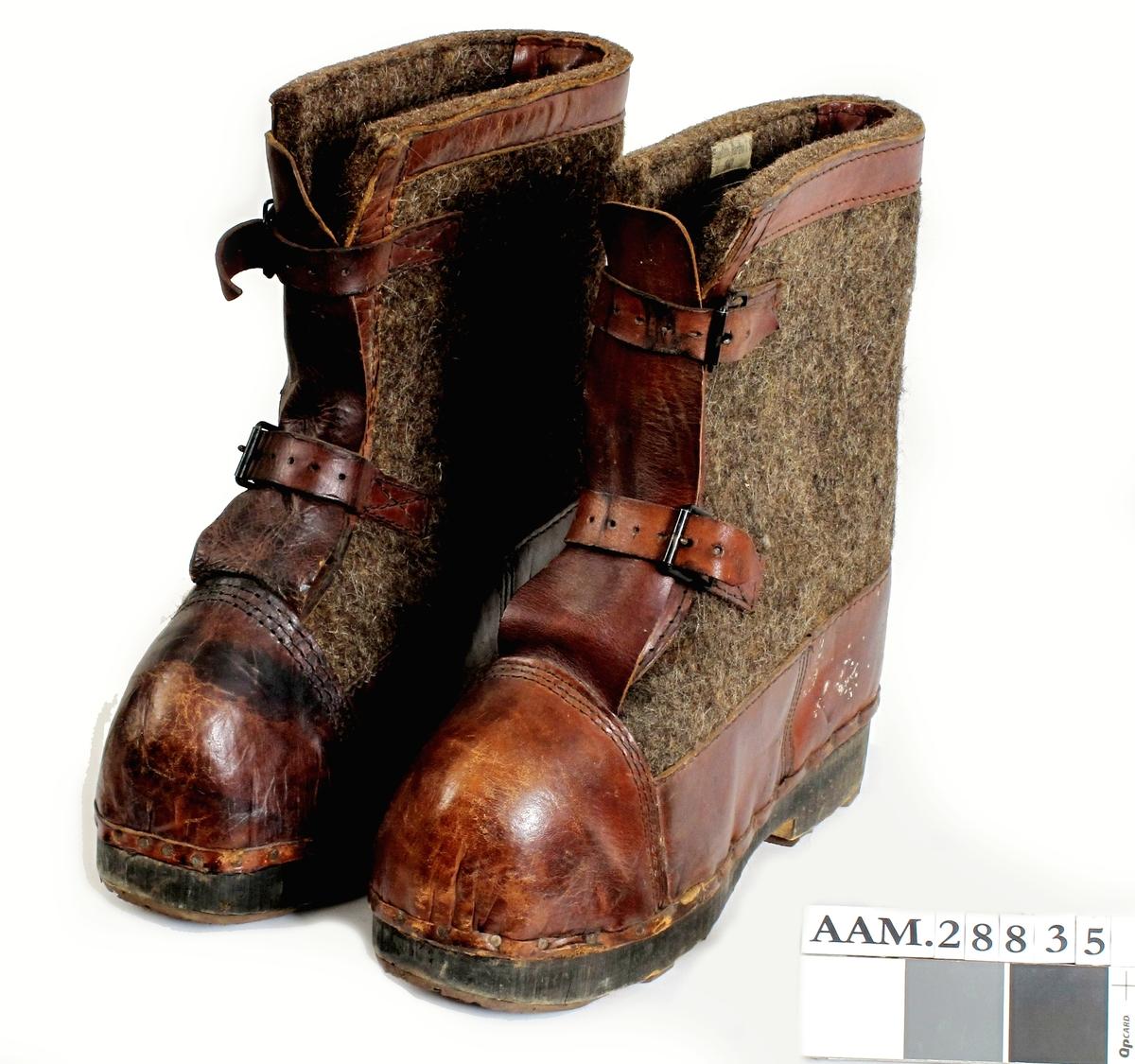 Støvler av filt, trolig ull. Slitebeslag av lær, spenner etc av metall. Såler av tre.