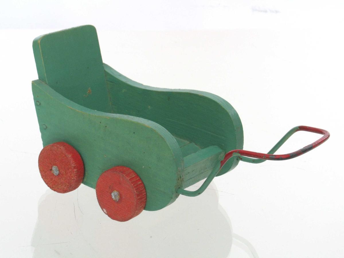 Liten dukkevogn med høyt ryggstø, svungne sidekarmer og regulerbart fotbrett i fremkant. Håndtak i fremkant.