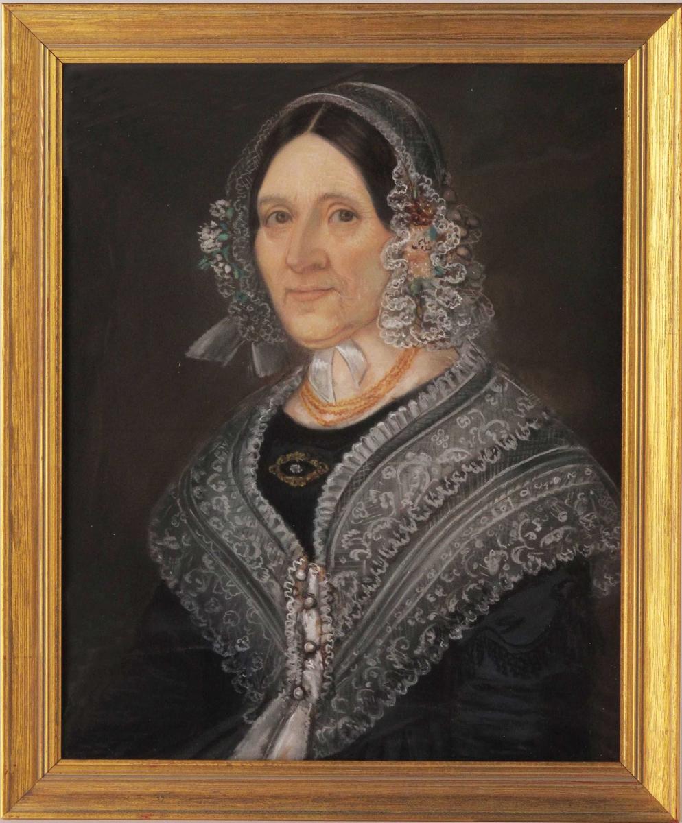 Portrett av middelaldrende kvinne, brystilde, halvt vendt mot sin høyre side. Mørkt glatt hår delvis skjult av hodeplagg. Kledd i . Usikker identifikasjon, men trolig kjøpmannsfrue fra Arendal.
