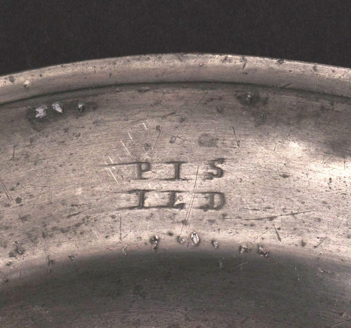 Tinnfat. med initialer  PIS og ILD (?)  Ustemplet.  Fat med svakt buet brem og en profilring ytterst langs kanten.   Tilstand: mørk bakside, nokså gjennomhullet i kanten og over midten.