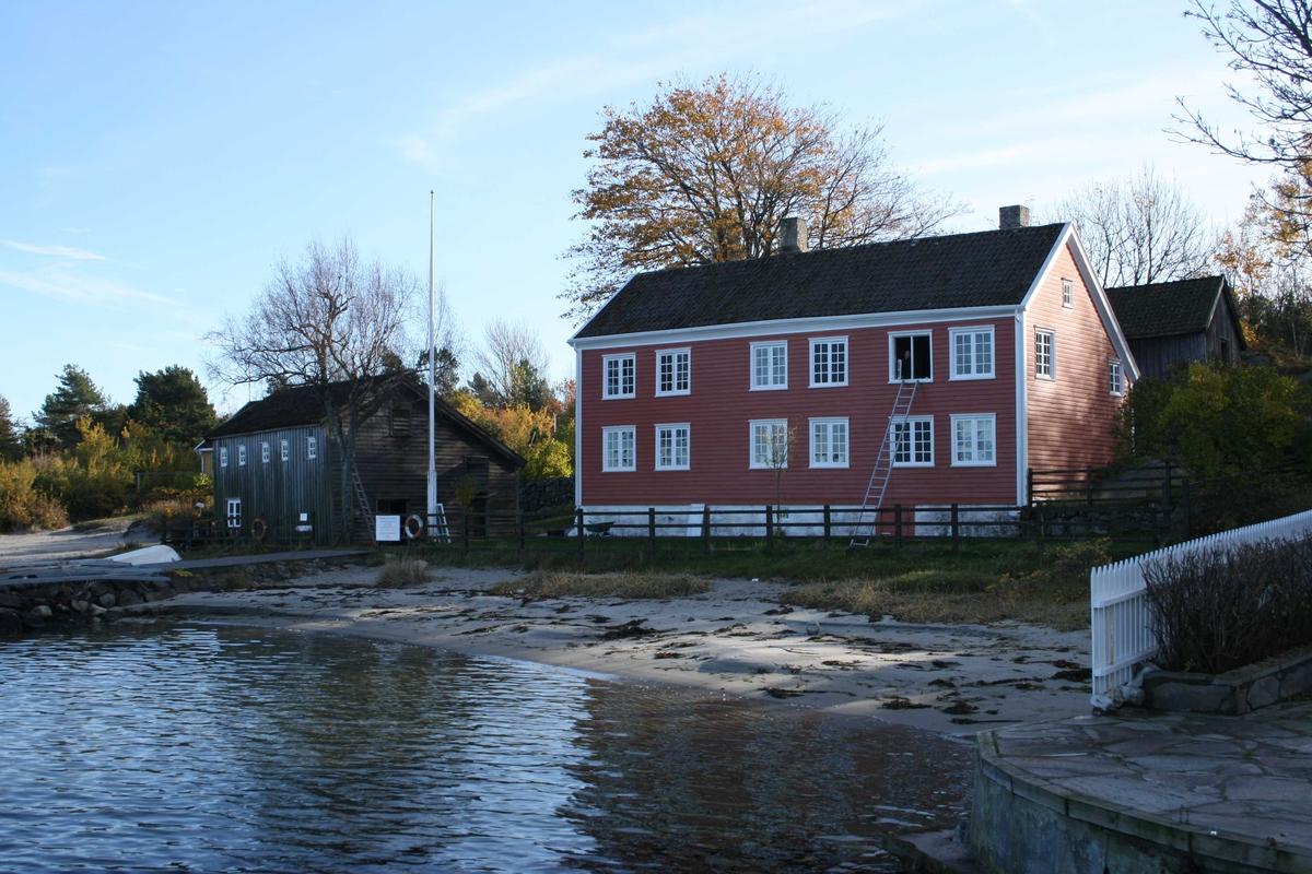 Merdøgaard, gårdstun sett fra V, sjøbod og våningshus t.v. og fjøs bak t.h.  Tunntreet, lønn, synlig over våningshuset.