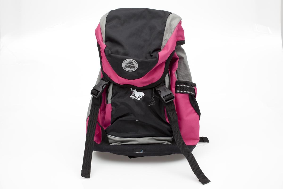 """En liten hare sitter på forlommen på skolesekken. Den er grå og har en rosa snute. Det er satt reflekser på sidene av sekken og på skulderremmene. Refleksene er rombeformet. Emblemet med """"Fjellsport"""" er oval og og på dette er trykt et fjellparti."""