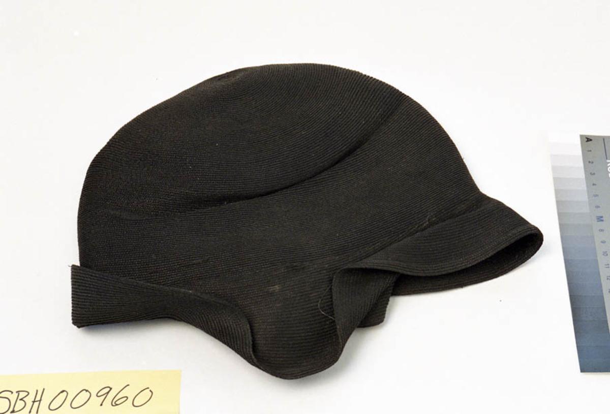 Teknikk: Sydd. Mønsteret i stoffet er som i heklete tekstiler, dvs. at det går i sirkler med utgangspunkt i midten. Tverrsnitt i et hull viser at  hatten  er laget av bånd, flettet av grove tråder, som er sydd sammen.  Form: Hatten er rund og dyp, slik at den kan tres langt nedover hodet. Bremmen går i ett med hatten og henger ned, men ser ut til å ha vært brettet opp foran og bak og sydd fast i denne posisjonen. På innsiden er det et fôr, som kan være bomull. Og innerst, på innsiden av toppen, er det sydd på et merke (ant. plast). Tilstand: Merket på insiden er meget sprøtt, og fôret sitter løst. Det ser ut til at noen sømmer som skulle holde bremmen er gått opp. Hatten har dermed ikke sin opprinnelige form. Ellers er stoffet i god behold.