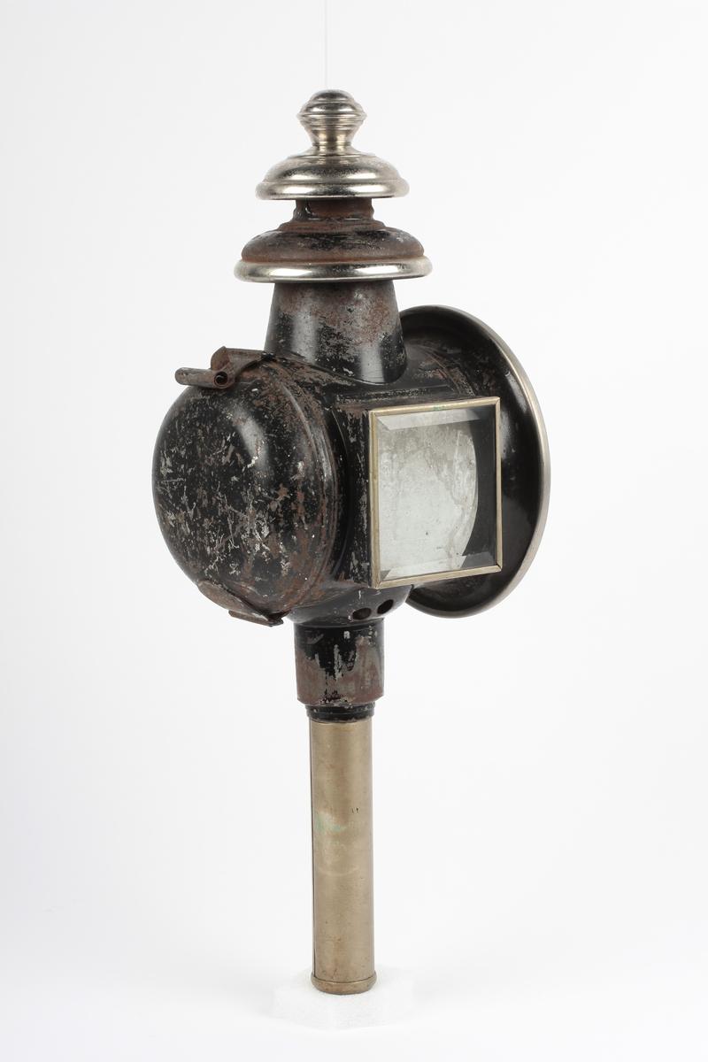 Sylinderformet lykt med rundt glass i fronten. Rektangulært glass i siden. Lokk på baksiden. Topp med to hvelvede skåler og rund knapp øverst. Sylindrisk stolpe nederst til feste. Innkjøpt etter trygdekassen (H.J.O. Gaarder) Form: Sylinderformet