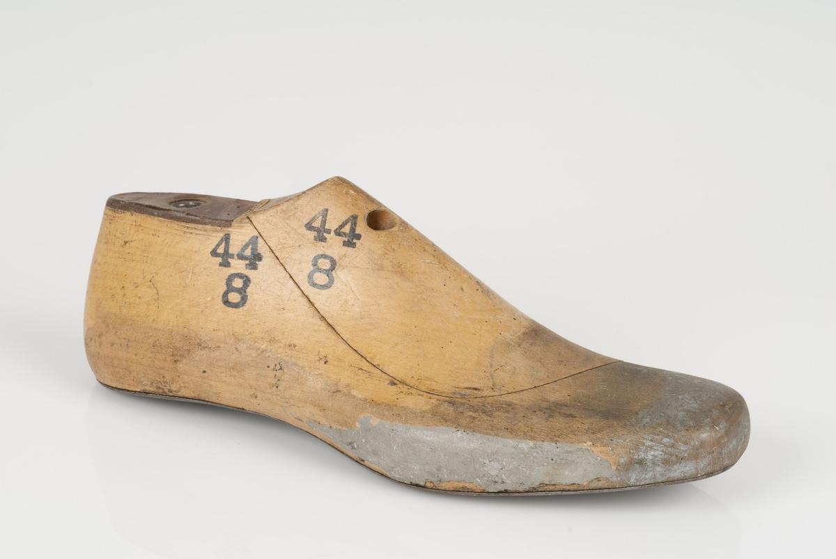 En tremodell i to deler; lest og opplest/overlest (kile). Høyrefot i skostørrelse 44, og 8 cm i vidde. Såle i metall. Lestekam i skinn.