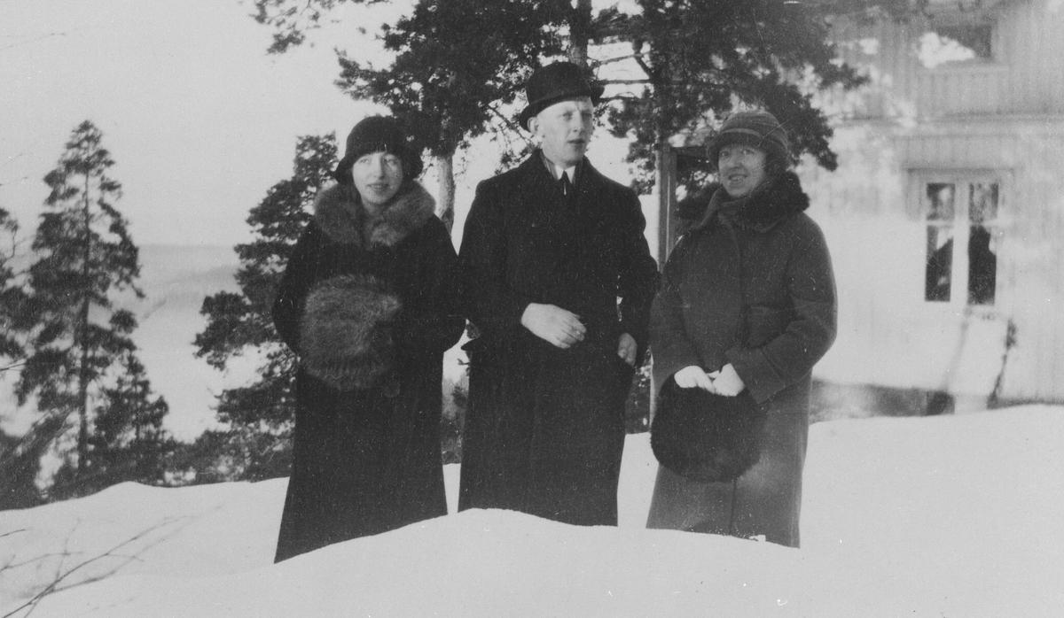 To søstre og en bror (Edith, Signe, Birger) vinterkledd utenfor huset.