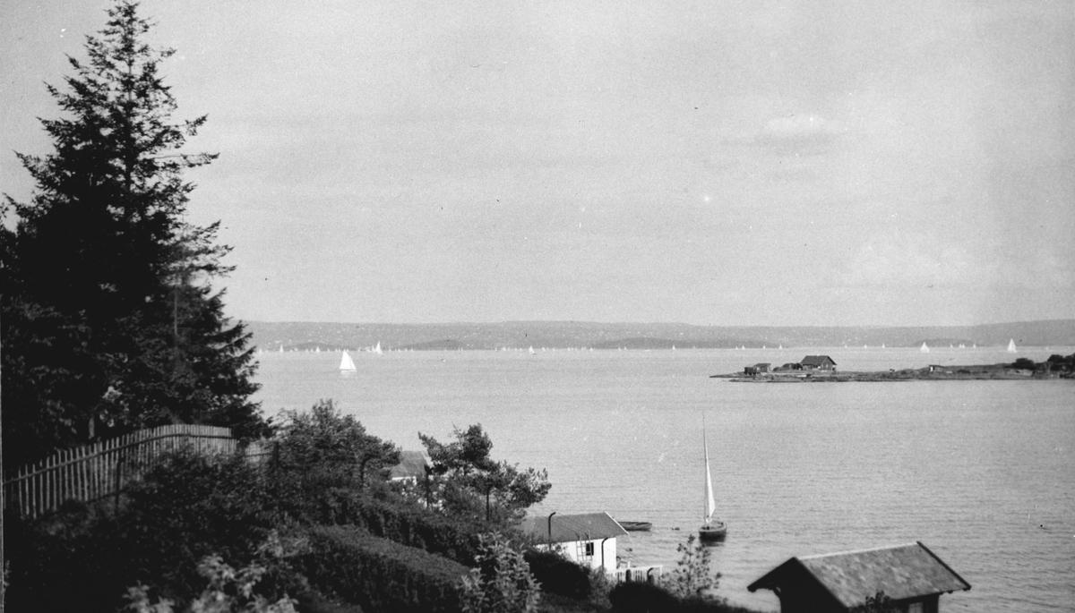 Utsikt til badehus, sjø, seilbåt.
