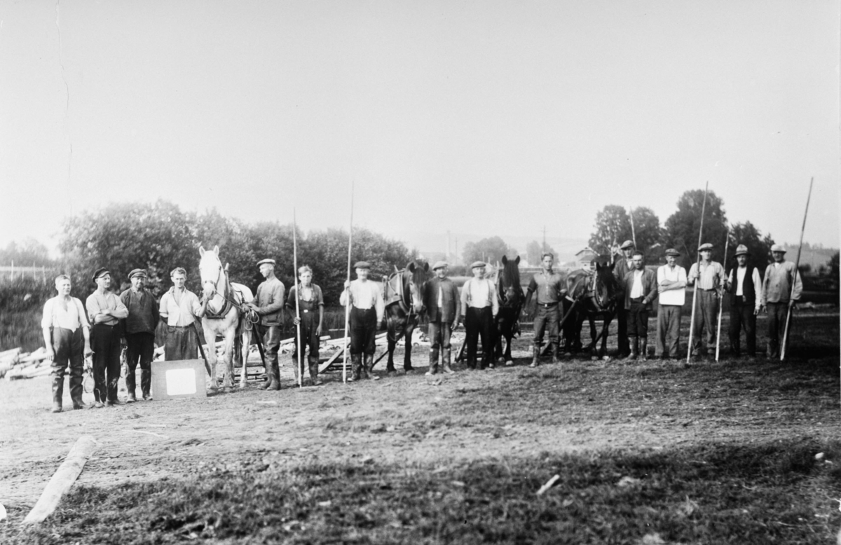Arbeidsfolk ved landkjøring av søkktømmer. Karene tilhørte Lertangen Sjunk. Tre hester,  I bakgrunnen; Nerdrum Bruk og Liertangen