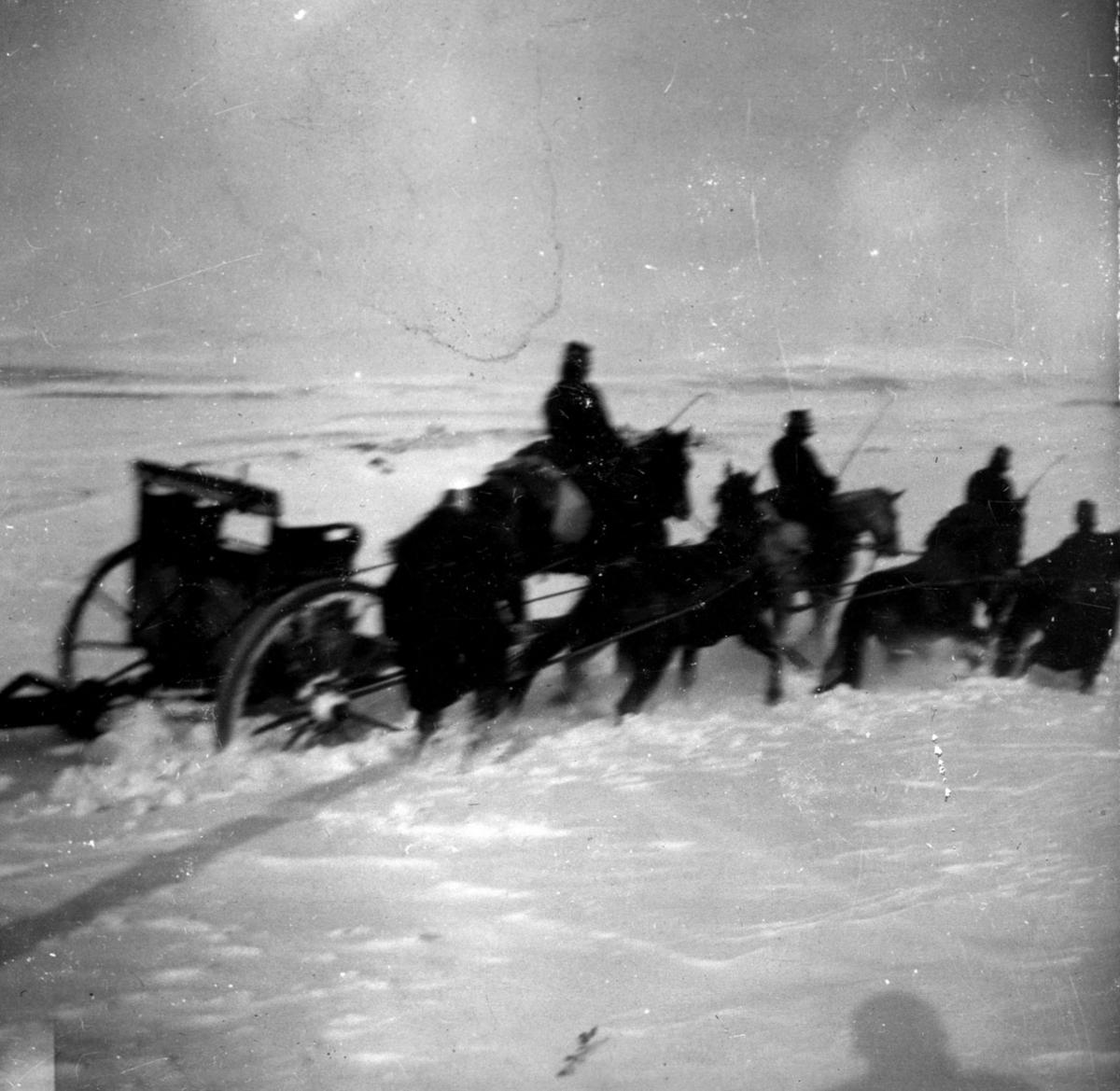 Militær vinterøvelse. Ryttere, hester, kanon fast i snøen