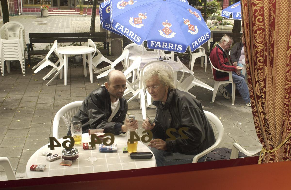 Første dagen etter innføring av røykeloven 2004. Flamenco Pizza & Pub. Parasoller og hagemøbler. To menn sitter ved et bord og røyker. Bildet er tatt innefra, gjennom vinduet.