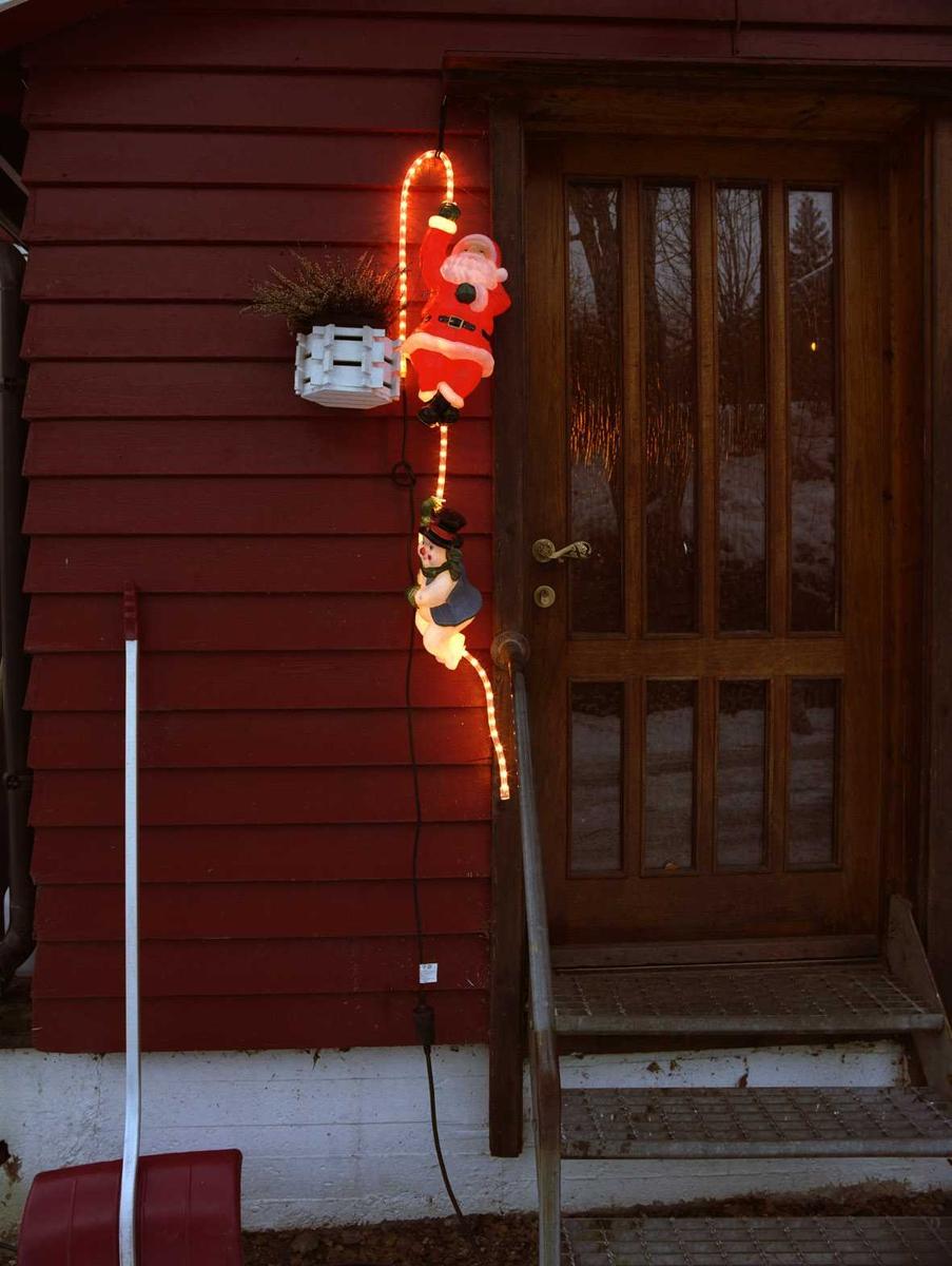 Julebelysning.    Lysende nisee og snømann klatrer på lysslange ved dørparti på enebolig.